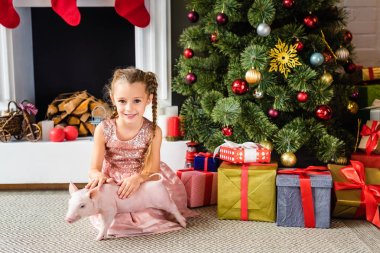 adorable little child playing with pig and smiling at camera at christmas time