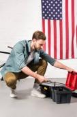 pohledný mladý muž uvedení nastavitelný klíč v poli nástroje v přední části zdi s americkou vlajkou