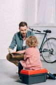 Photo  man talking and reading book to little son sitting on tools box in bicycle workshop
