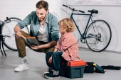 Photo smiling man reading instructions to little son sitting on tools box in bicycle workshop