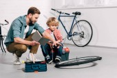 Photo man with book pointing by hand at bicycle wheel to little son in workshop