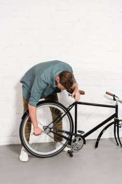 young man repairing bicycle by adjustable spanner