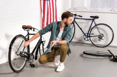 selective focus of young repairman fixing bicycle by adjustable wrench