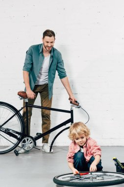 adorable little boy fixing wheel by pliers while his father standing behind with disassembled bicycle in workshop