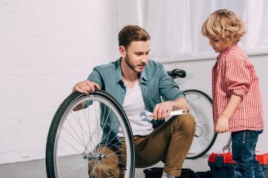 man with adjustable spanner sitting near bicycle wheel and talking to little son in workshop