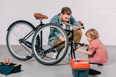 man helping little boy fixing bicycle near tools box in workshop