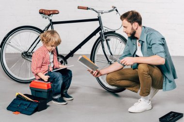 kid sitting with digital tablet while father reading book at bicycle workshop