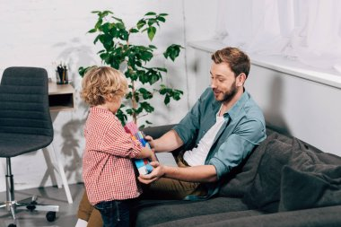 child bringing colorful plastic blocks to happy father at home