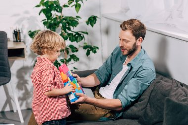 side view of little boy bringing colorful plastic blocks to smiling father at home