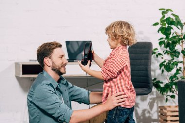 side view of little boy putting on headphones on smiling father