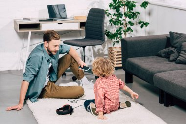 rear view of little boy sitting on floor with father holding smartphone with headphones at home