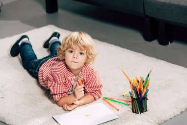 Selective focus of little boy painting by marker at home stock vector