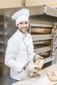 Fényképek mosolyogva szakácsok egységes gazdaság a friss kenyér sütő közelében baker