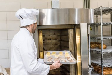 male baker in chefs uniform putting raw dough in oven