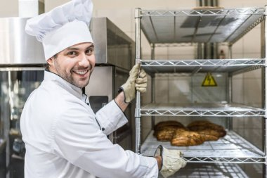 smiling male baker with hot baked bread on rack