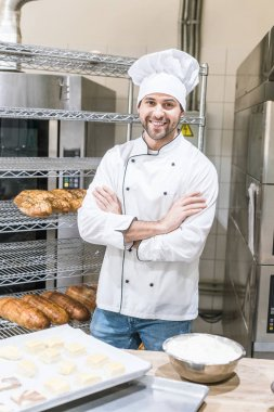 smiling male baker standing with arms crossed at kitchen