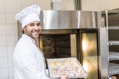 smiling baker in white chefs uniform putting baking tray with uncooked dough in oven