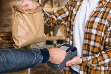 close up of seller holding paper bag while customer paying for purchase with credit card at bakery