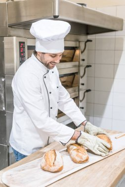 smiling baker standing near oven with fresh baked bread on wooden counter