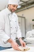 Baker v uniformě bílých kuchaři hnětení těsta na stole pekárna