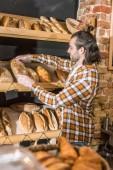 Boční pohled na mužské prodávajícího uvedení čerstvě upečený chléb na dřevěné police