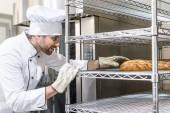 Fotografie Side view of baker in gloves taking bread