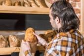 Muž prodávající uvedení čerstvý chléb v papírový sáček