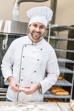 smiling cheerful baker with raw products at kitchen