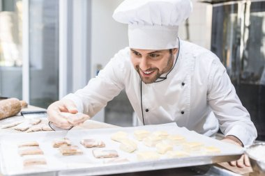 Baker in chefs uniform smiling and laying uncooked dough on tray