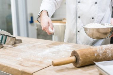 Cropped view of cook hands scattering flour on wooden table