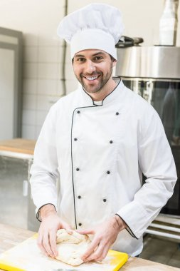 Handsome chef smiling and kneading dough on cutting board