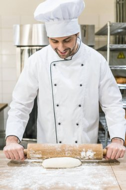 Smiling baker rolling out uncooked dough on wooden table
