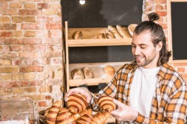 Handsome seller holding pastry in bakehouse stock vector