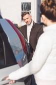 Žena otevírá dveře od auta a člověk dívá a usmívá se na ulici
