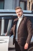 Pohledný muž, který stojí poblíž auto s otevřené dveře