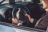 Muž sedí a vozem v denní