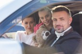 Fotografie  Preteen daughter sitting in car with teddy bear and parents