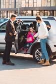 Preteen dcera sedí v autě s otevřené dveře a drží za ruku a maminka