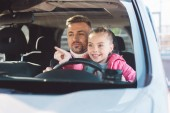 Daughter sitting in car with dad and pointing at car window