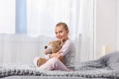 Photo Cheerful kid holding teddy bear and sitting on bed