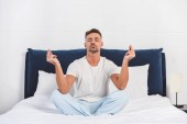 Pohledný muž cvičení jógy v pyžamu