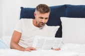 Handsome man reading newspaper in bed