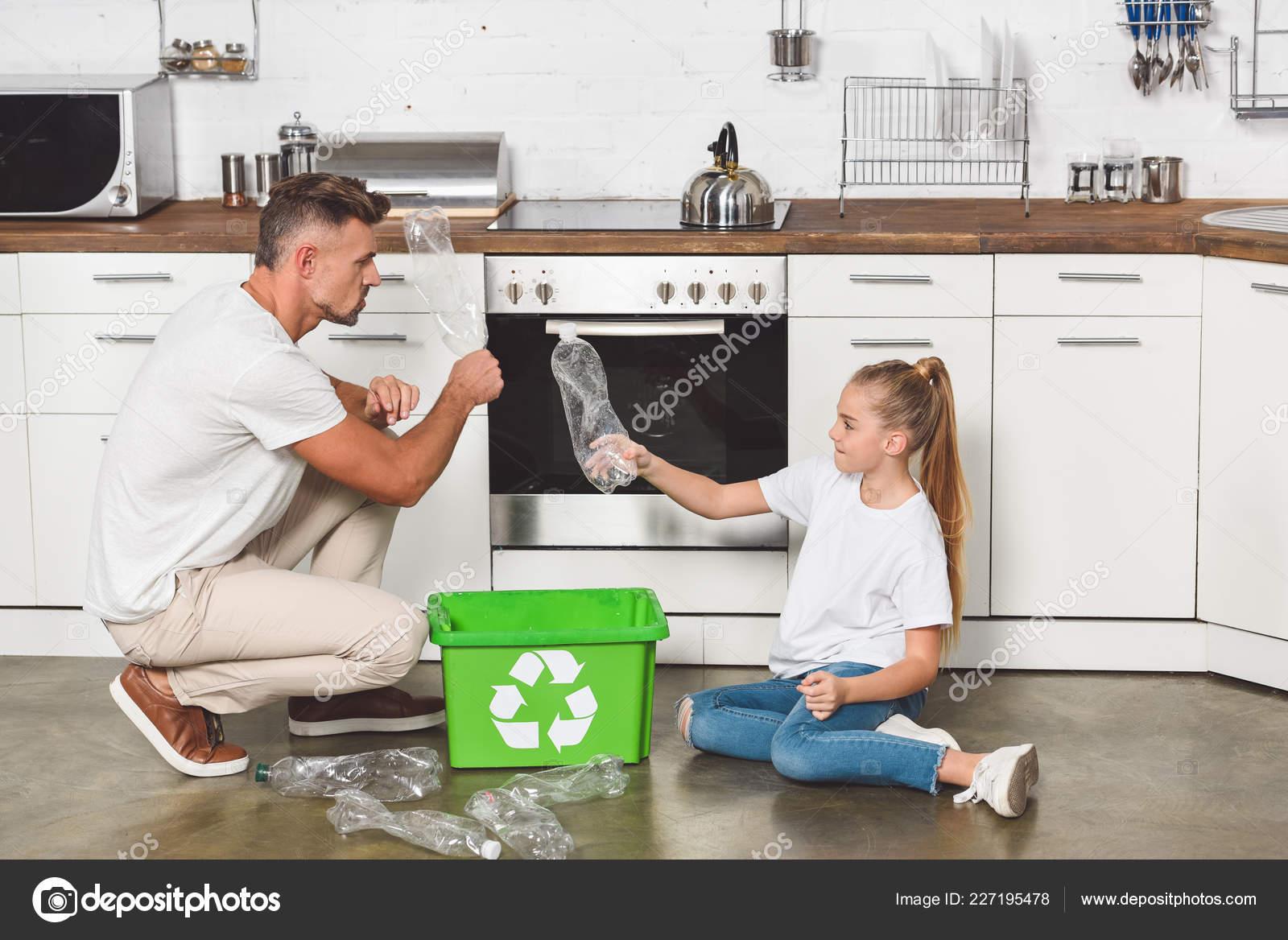 Vater Und Tochter Sitzen Auf Boden Kuche Und Leere Plastikflaschen
