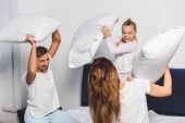 Fotografie Cheerful family having pillow fight in bedroom