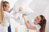 Cheerful mother and daughter having pillow fight at home