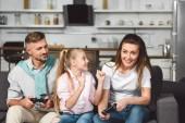 šťastná rodina hraje videohry společně v obývacím pokoji