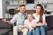 Dcera jíst popcorn z misky při sledování televize s rodiči