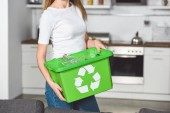 Photo cropped view of woman holding green box with recycle sign and empty plastic bottles