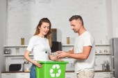 Photo adult couple putting empty plastic bottles in recycle green box at kitchen