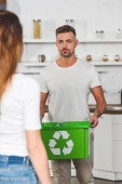 Photo adult man holding green box with recycle sign and looking at woman